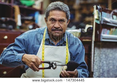 Portrait of shoemaker hammering on a shoe in workshop