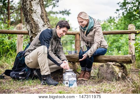 Man and woman take break from hiking and prepare food on camping stove