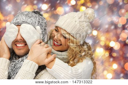 people, christmas, holidays and new year concept - happy family couple in winter clothes playing guess who game over holidays lights and snow background