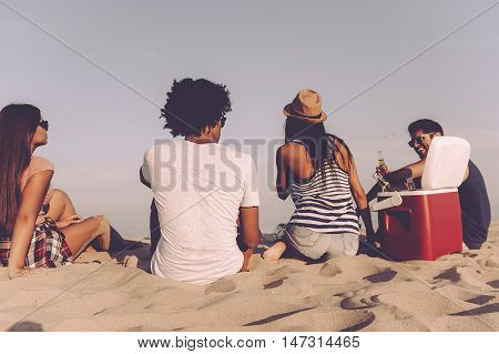 Relaxing with friends. Rear view of four cheerful young people spending nice time together while sitting on the beach and drinking beer