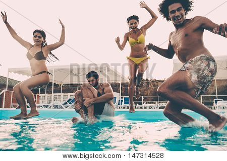 Pool party. Group of beautiful young people looking happy while jumping into the swimming pool together