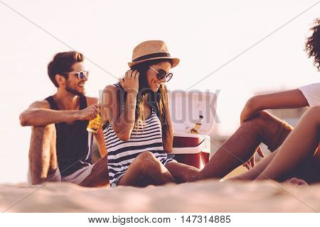 Beach time with friends. Cheerful young people spending nice time together while sitting on the beach and drinking beer