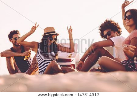 Enjoying beach party. Cheerful young people spending nice time together while sitting on the beach and drinking beer