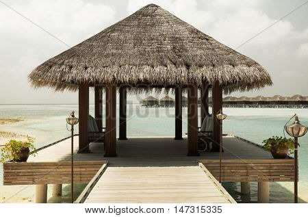 travel, tourism, vacation and summer holidays concept - patio or terrace with canopy on maldives beach sea shore