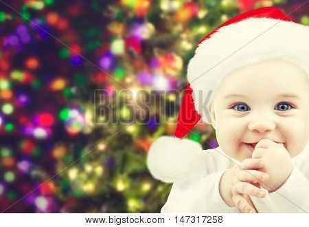 christmas, babyhood, childhood and people concept - happy baby in santa hat over holidays lights background