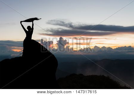 Silhouette of women spreading hand on the top of mountain at sunset