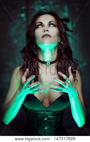Halloween. Witch creates magic. Beautiful and sexy woman with a mystical light