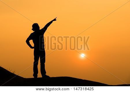 Silhouette of a woman point her hand to the sky