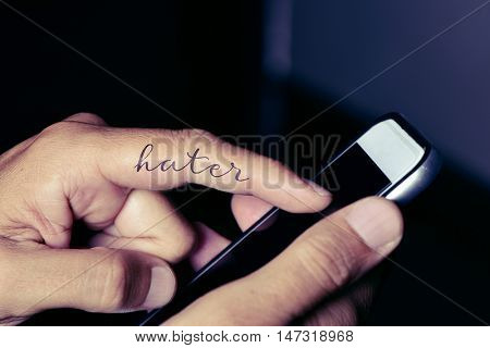 closeup of the hand of a young caucasian man using a smartphone with a simulated tattoo of the word hater in his forefinger