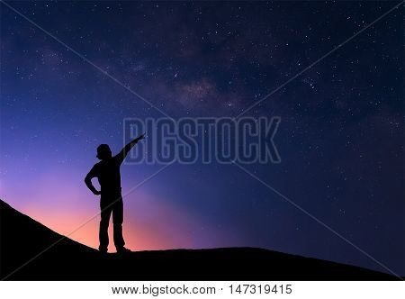 Sillhouette of woman standing next to the milky way and pointing on a bright star.