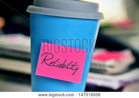 closeup of a pink sticky note with the word reliability in a blue cup of coffee or tea on an office desk