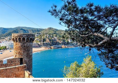 a view of the walls and towers of the Vila Vella, the old town, of Tossa de Mar, Spain with the Platja Gran beach in the background