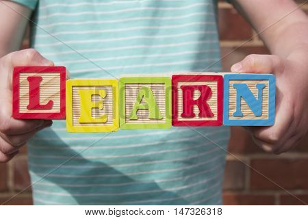 A girl holding wooden blocks spelling the word 'LEARN'. The girl is outdoors on a brick wall background.
