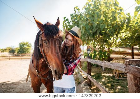 Pretty redhead young woman cowgirl taking care of her horse on farm