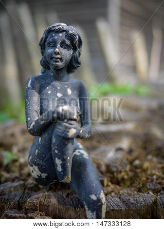 Small old damaged figurine of a female on a cut tree
