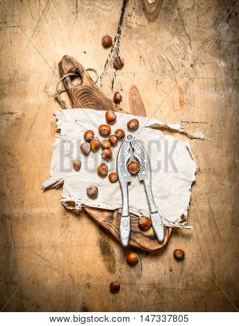 Nuts with Nutcracker and shell. On a wooden table.