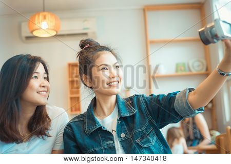 Portrait Of Two Happy Young Asian Woman Take Selfie In Cozy Coffee Shop