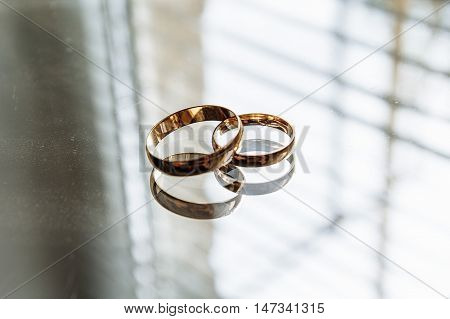 wedding rings on the mirror , window light
