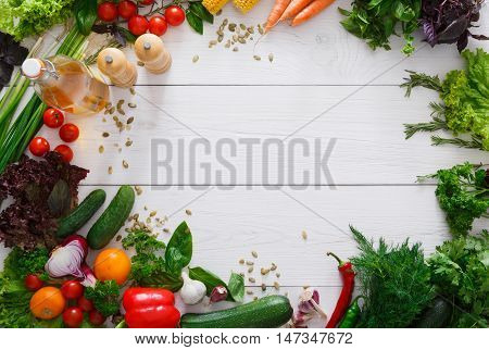 Border on white wood for menu or recipe, fresh organic vegetables, spices, greens and herbs background. Healthy natural food on rustic wooden table with copy space. Cooking ingredients top view