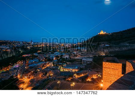 Top View Of Illuminated Tbilisi, Abanotubani District And Tabor Monastery Of The Transfiguration, Built On Taboris Mta Or Tabor , Favor, Mount. Blue Evening Sky And Moonlight Background, Georgia