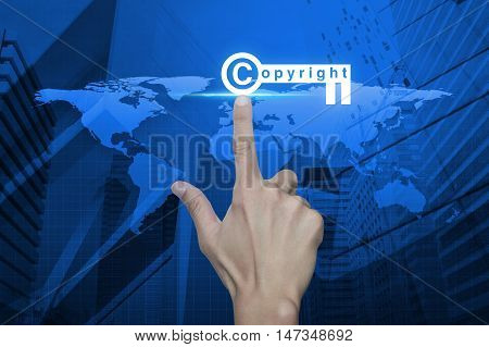 Hand pressing copyright key icon over map and city tower background Copyright and patents concept Elements of this image furnished by NASA