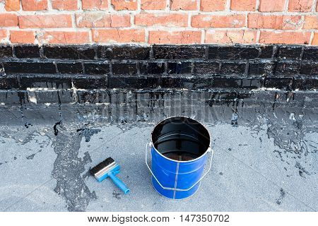 Ceiling brushes and a bucket of bitumen primer for waterproofing against the background of a brick wall