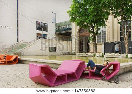 VIENNA, AUSTRIA - JUN 10, 2016: Man having rest in outdoor bench in modern style near Leopold Museum on June 10, 2016. Museum has largest collections of Austrian art featuring Egon Schiele Gustav Klimt