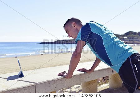 a young caucasian sportsman wearing sport clothes doing incline push-ups exercises outdoors, while is watching a training video in his tablet computer, next to the sea