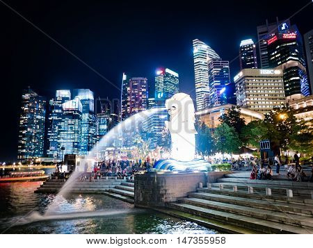 SINGAPORE - AUGUST 24 2016 : The Merlion fountain in front of business buildings at night of Marina Bay in Singapore