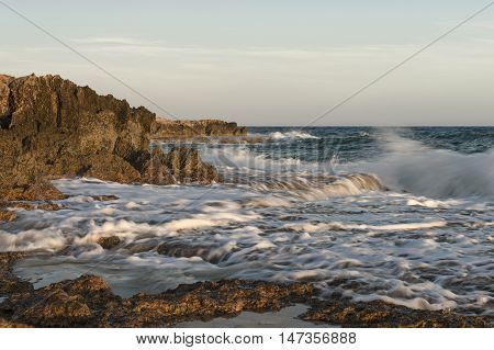 Rocky shore. Sunset over the heavy sea