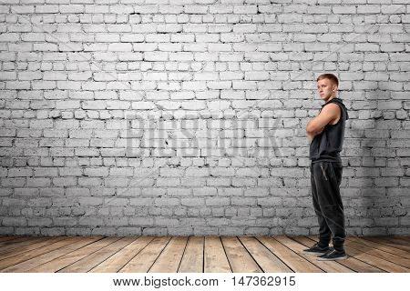 Front view of muscled young man standing with his arms folded looking at the camera, on the background of white brick wall. Wellbeing. Muscleman. Workout and fitness.