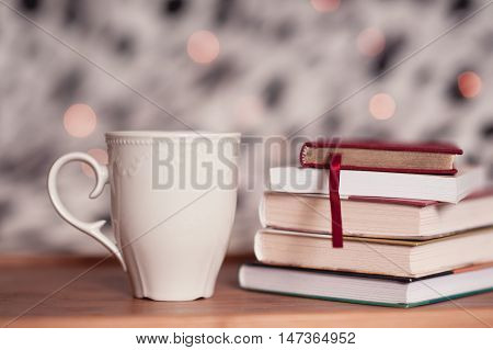 Cup of tea staying with stack of books on wooden table over christmas lights