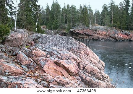 Imatra. Finland. Granite boulders on The Vuoksi River next to The Imatrankoski Rapids. On the background is The Kruununpuisto Park