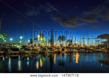 Sailing boats and yachts docked at the Ala Wai Harbor the largest yacht harbor of Hawaii reflecting in the sea. Honolulu harbor by night Oahu Hawaii.
