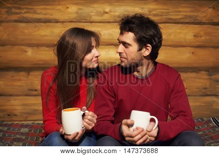 man and woman drinking tea at his home. young couple in love with mugs in hands