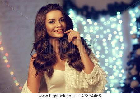 Close up bust length portrait of young smiling happy woman with long brunette curly hair posing in christmas decorated interior against lights bokeh