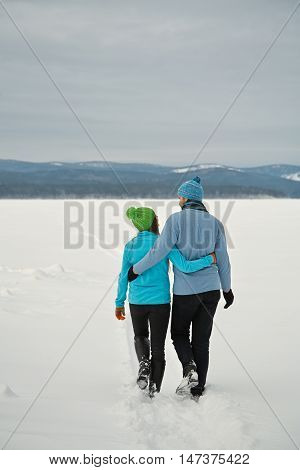 Young happy couple in love in the winter. Man and woman walking outdoors