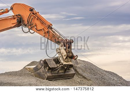 Excavator arm and bucket - Close up with the details of an orange excavator arm and bucket in a pile of ballast