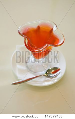 Jelly in glass plate, fruit gelatin dessert beige background. soft focus poster