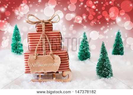 Sleigh Or Sled With Christmas Gifts Or Presents. Snowy Scenery With Snow And Trees. Red Sparkling Background With Bokeh Effect. Label With German Text Willkommen Means Welcome