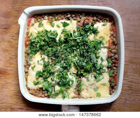 Tasty lentils, baked with cheese and tomato with sauce in square pan, sprinkled with green parsley on the vintage wooden table surface. Top view closeup