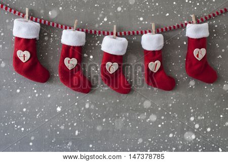 Nicholas Boots As Advent Calendar Hanging On A Line. Cement Wall As Modern Background With Snowflakes. Textile Shoes With Hearts With Numbers 4 Till 8 For St Nicholas Day