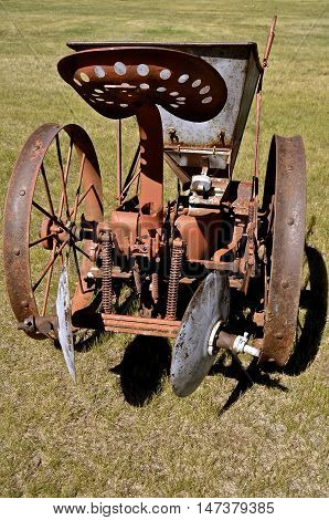 An old horse drawn one row potato planter with a seat for the operator