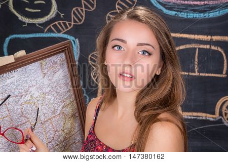 Young student girl in red dress reports on geography classes with u.s.a. map poster