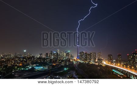 Powerful Lightning bolt strikes over Toronto City in a strong, hot, and humid thunderstorm.  Stormy night in August, Toronto skyline with weaker flashes of lightning behind the city.