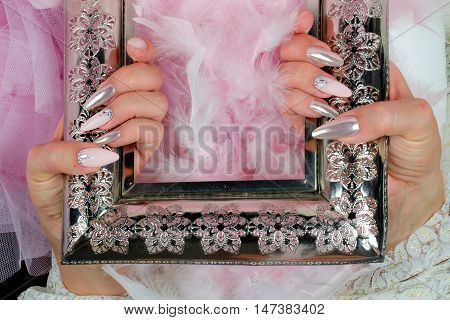 beautiful fingernails decorated with pink and pearl colors with rhinestones that reflect the light and create extraordinary effects Star shake an ancient finely decorated metal frame