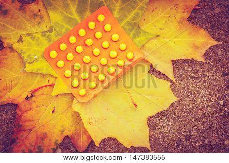 Health nature medicine drug symbolism concept. Pills on leaf. Package of medicine lying on maple foliage.