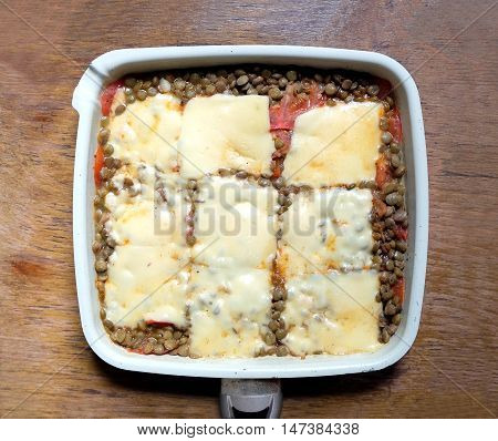 Tasty lentils, baked with cheese and tomatoes with sauce in square pan on the vintage wooden table surface. Top view closeup