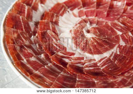 Circular decorative arrangement of iberian cured ham on plate. Selective focus point