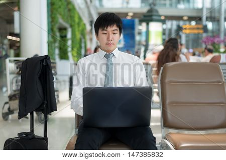Asian young business traveler using laptop computer in airport lounge while waiting flight at airport. Business travel concept.